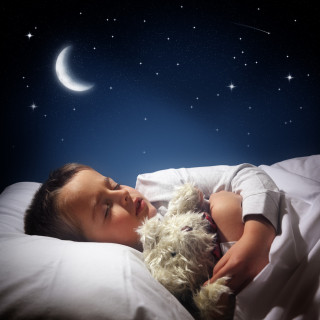 Child sleeping and dreaming in his bed under the moon, stars and